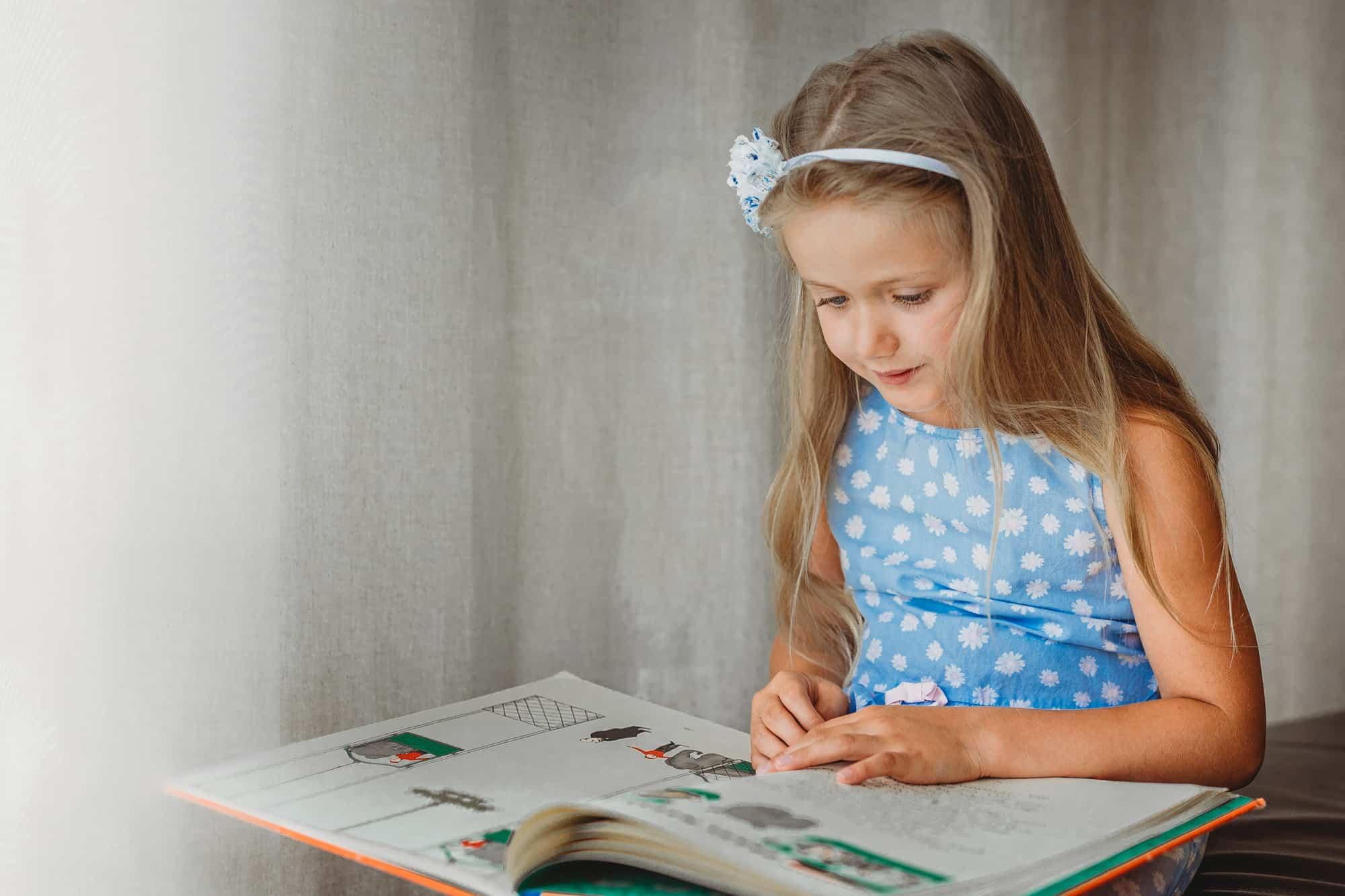 Mädchen sieht sich ein Märchenbuch an, fotografiert von Ursula Leopold, Sujetbild zum Blogartikel 30 Beschäftigungsideen
